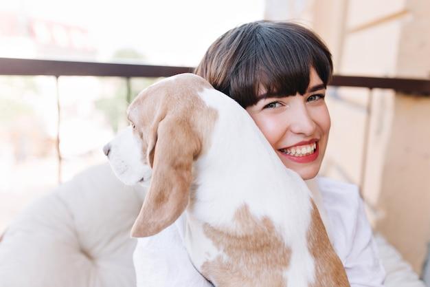 비글 강아지를 들고 어두운 갈색 머리와 웃는 여자의 클로즈업 야외 초상화