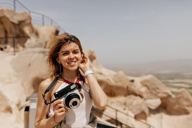 レトロなカメラを持って、日光の下で古い岩の間を歩いて笑顔の幸せな女の子の屋外の肖像画を閉じる