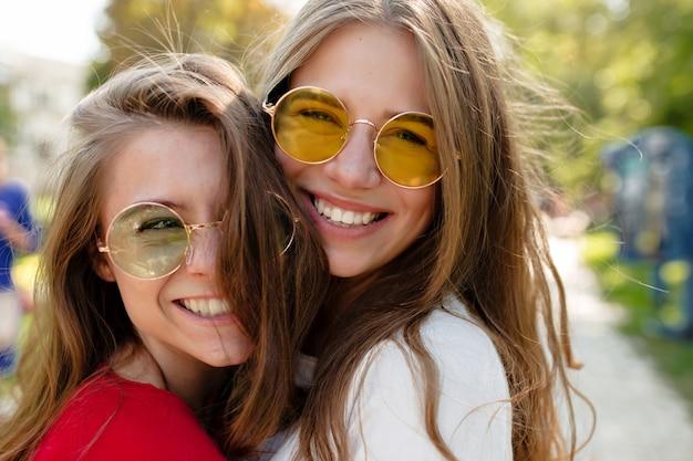 明るい眼鏡笑顔で日当たりの良い公園でポーズをとって2つの陽気な女性の親友の屋外のポートレートを閉じます。外一緒に無料の本を過ごす2つの面白い女性の友人