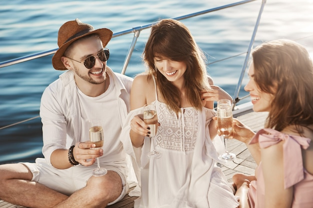 Close-up outdoor portrait of three friends talking and drinking champagne while sitting on board of boat and enjoying sunlight.