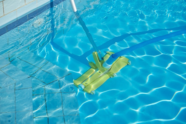 Close-up of outdoor swimming pool underwater, cleaning vacuum tube.