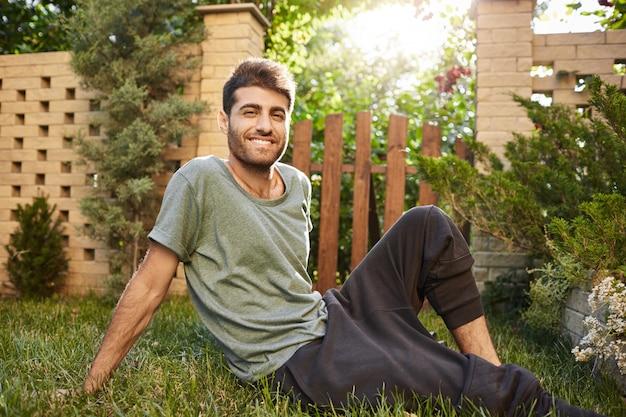 웃 고, 잔디에 앉아, 휴식 파란색 티셔츠와 스포츠 바지에 성숙한 매력적인 수염 된 백인 젊은 남자의 야외 초상화를 닫습니다