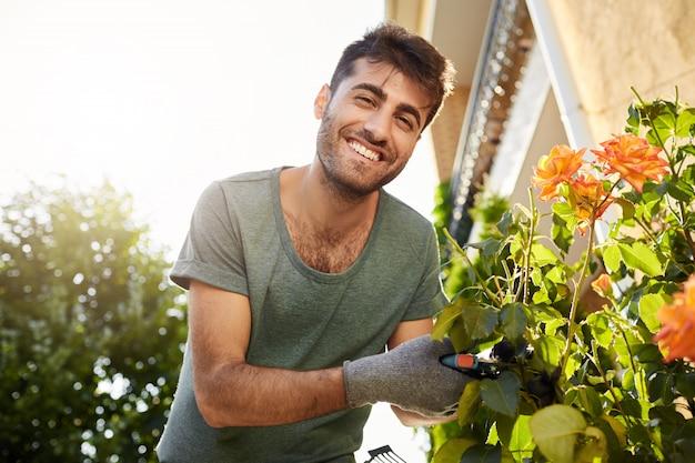 파란색 티셔츠 웃고, 도구로 정원에서 일하고, 잎을 자르고, 꽃에 물을주는 젊은 쾌활한 수염 난 남자의 야외 초상화를 닫습니다