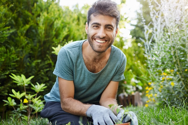 Close up outdoors portrait of young attractive bearded caucasian male gardener in blue t-shirt smiling in camera, planting seeds in garden, watering plants.