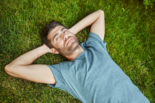 Close up outdoors portrait of young attractive mature bearded hispanic man in blue t shirt looking in camera, lying on ground with relaxed face expression.