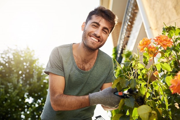 Close up outdoors portrait of young cheerful bearded man in blue t-shirt smiling, working in garden with tools, cutting leaves, watering flowers