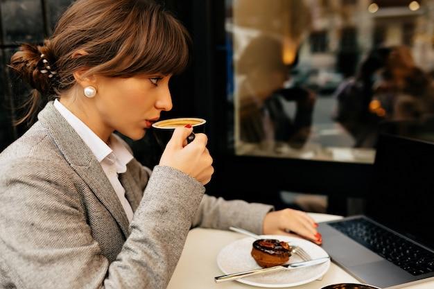 Крупным планом снаружи портрет деловой женщины, одетой в пиджак и блузку, перерыв на кофе во время работы фото высокого качества