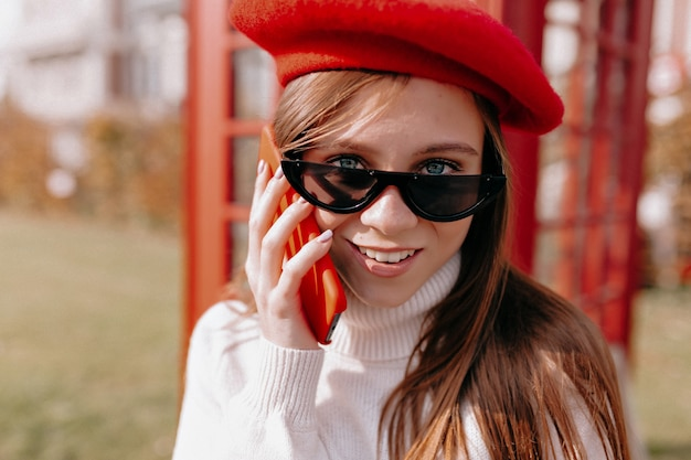 赤い帽子をかぶって効果的なスタイリッシュな現代女性の外の肖像画をクローズアップ