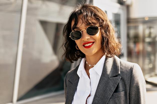 街の背景にカメラでポーズをとってカジュアルな服を着て短い髪型と赤い口紅で笑顔のきれいな女性の外の肖像画をクローズアップ