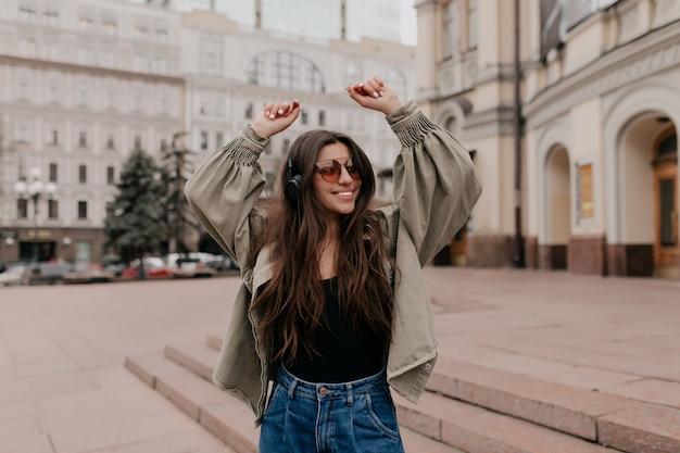 좋아하는 음악을 즐기는 헤드폰으로 도시에서 산책하는 재킷을 입고 긴 머리를 가진 웃는 예쁜 여자의 외부 초상화를 닫습니다