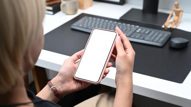 Закройте вверх по взгляду плеча женщины, держащей смартфон с белым экраном.