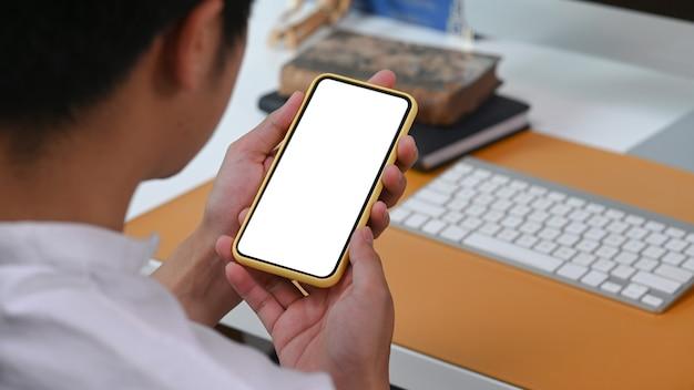 Закройте вверх по взгляду плеча молодого человека, держащего смартфон с пустым экраном.