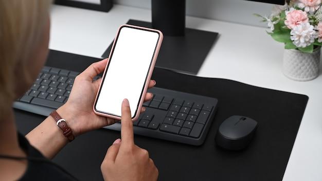 Крупным планом вид молодой женщины, сидящей на своем рабочем месте и использующей мобильный телефон, через плечо.