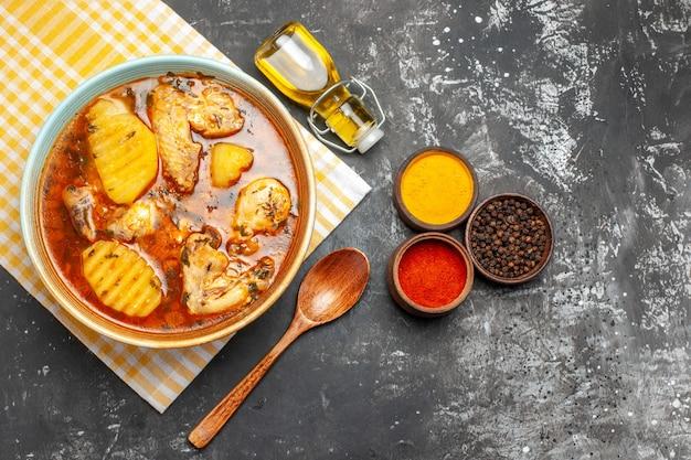 Крупным планом вид сверху на суп из различных специй с курицей и упавшим маслом на темноте