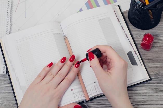 붉은 색으로 손톱을 칠하는 여성의 손에 대한 오버헤드 뷰 사진을 닫습니다