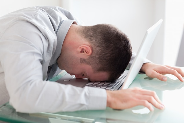 Close up of overworked businessman taking a nap on his laptop