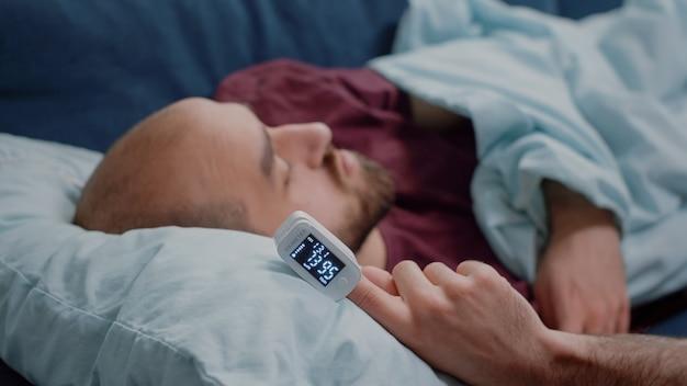 Primo piano dell'ossimetro a portata di mano della persona malata che riposa