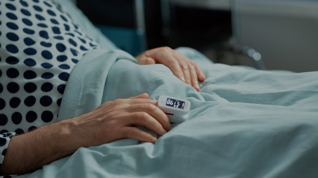 Close up of oximeter on patient in hospital ward bed at medical facility old man waiting on results ...