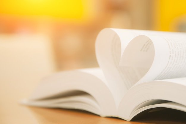 Close up page of book in heart shape at library.