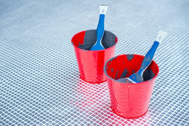 Close up of paint brushes in paint buckets outside.