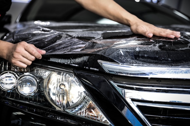Close up of paint protection film installation on front bumper of modern luxury car. ppf is polyurethane film applied to car surface to protect the paint from stone chips, bug splatter, and abrasion