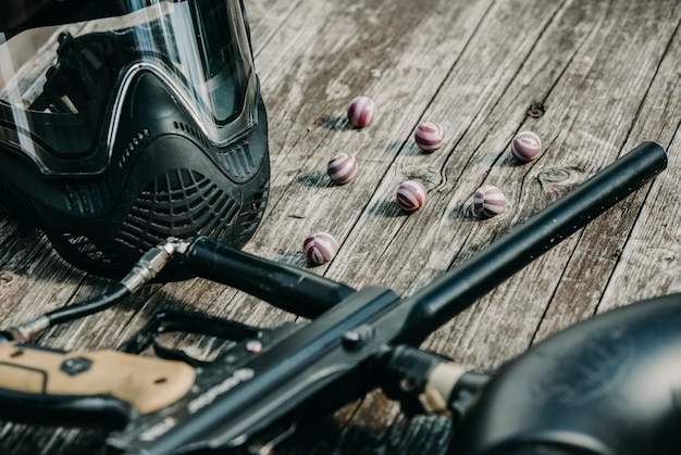 Close up of paintball gun, special balls and protective mask, equipment for playing paintball on a wooden table, action game concept