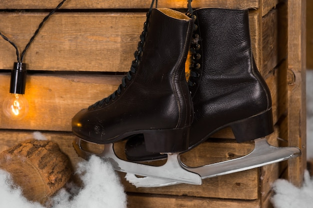 Close up pair of black leather ice skates hanging on the wooden wall with lighted bulb.