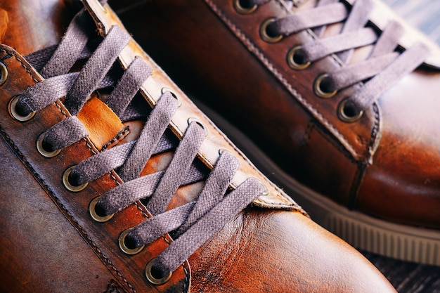 Close up of pair of men's brown leather shoes. lacing on shoes