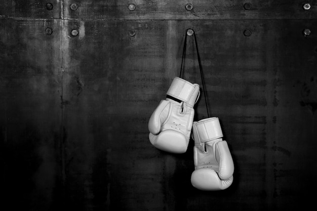 Close up pair of white leather boxing gloves hanging over black wall