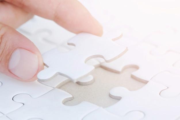 手のひらの手をクローズアップして、未完成の白いジグソーパズルの最後のピースをミッションに配置し、完全に完成させます