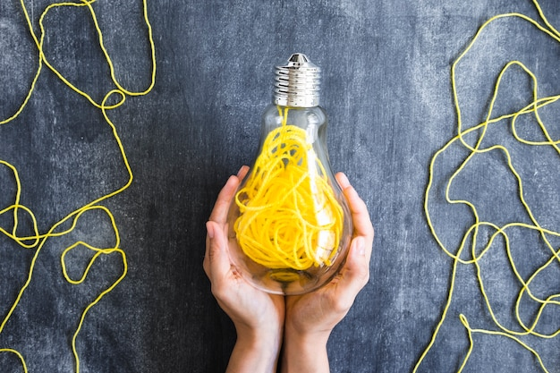 Close-up of palm holding transparent light bulb filled with yellow yarn against blackboard