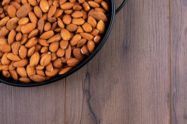 Close-up a pan of almond on wooden table. horizontal