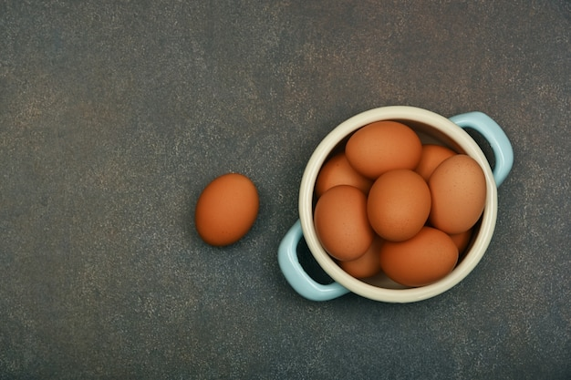 Close up pan bowl of brown chicken eggs on dark grunge table surface, elevated top view, directly above