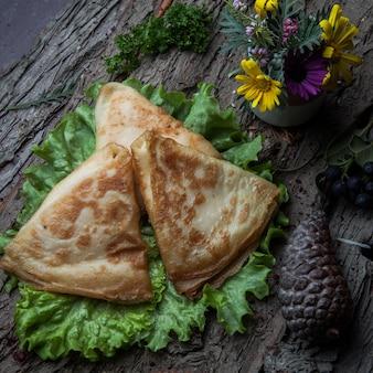 Pancake del primo piano con formaggio su un'insalata su una corteccia di legno