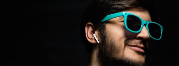 파란색 선글라스를 착용하는 무선 이어폰으로 젊은 남자의 근접 파노라마 초상화