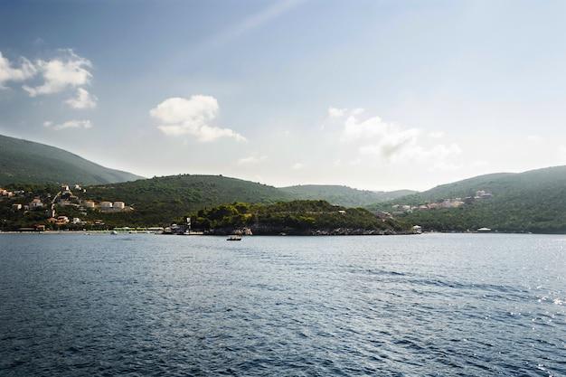 밝은 날 해안에 산이 있는 바다와 도시 경관의 클로즈업 파노라마 샷