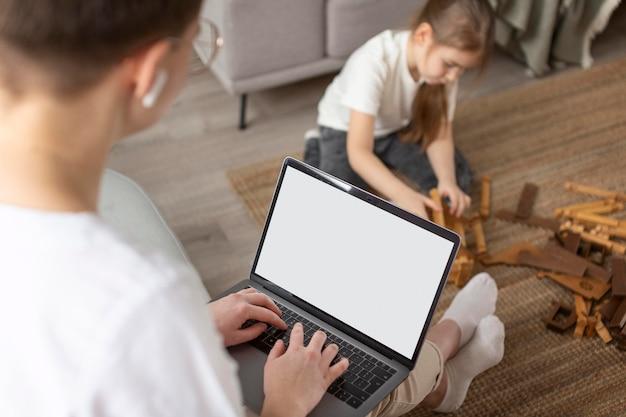 Chiuda in su genitore che guarda bambino e lavora