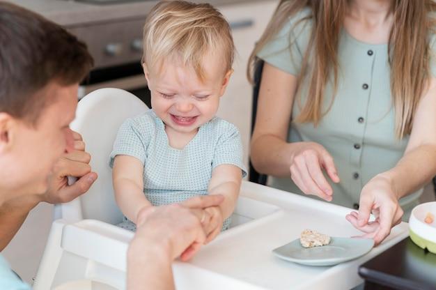 Chiuda sui genitori che alimentano il bambino
