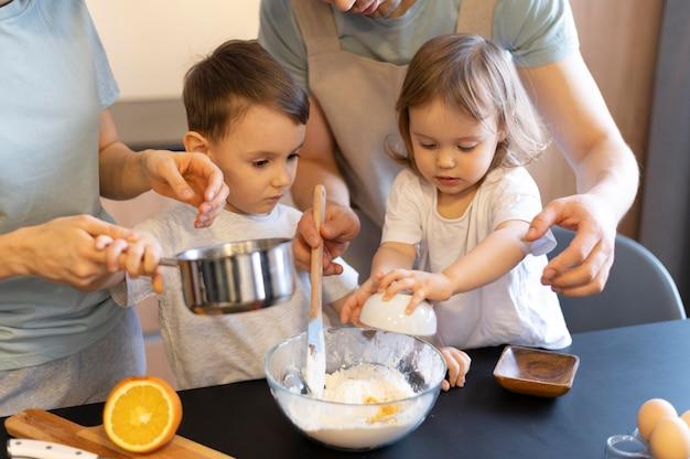 Genitori e bambini del primo piano che producono pasta