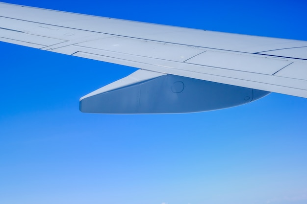 Close up of part of airplane wing with clear blue sky.