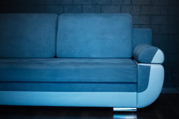 Close-up of part of blue sofa on the background of black brick wall.
