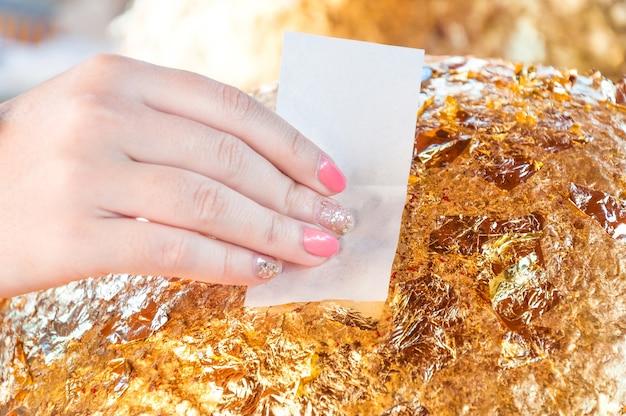 클로즈업, 돌볼에 금박을 입힌 손가락 손 여성 옻칠의 일부, 이름은 luuknimit, 손은 신성한 장소에서 금도금 부처, 태국의 불교도 믿음