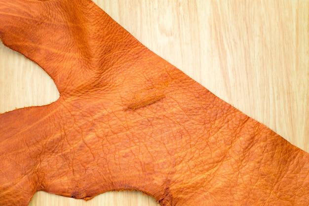 Закройте часть коричневой кожи, лежащей на деревянном столе