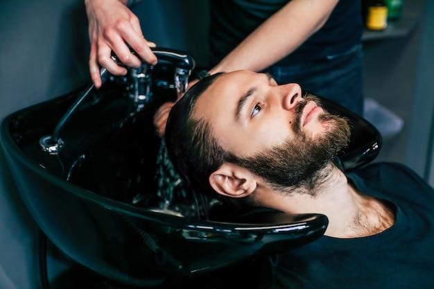 이발소에서 고객의 머리를 씻는 전문 미용사의 부분적인 보기를 닫습니다.
