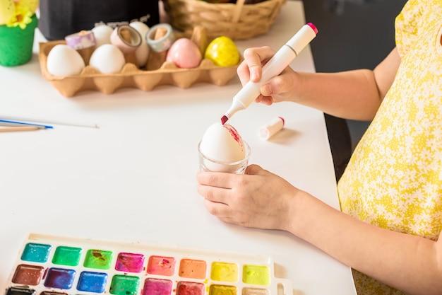 Частичный вид конца-вверх маленького ребенка картины пасхального яйца за столом.