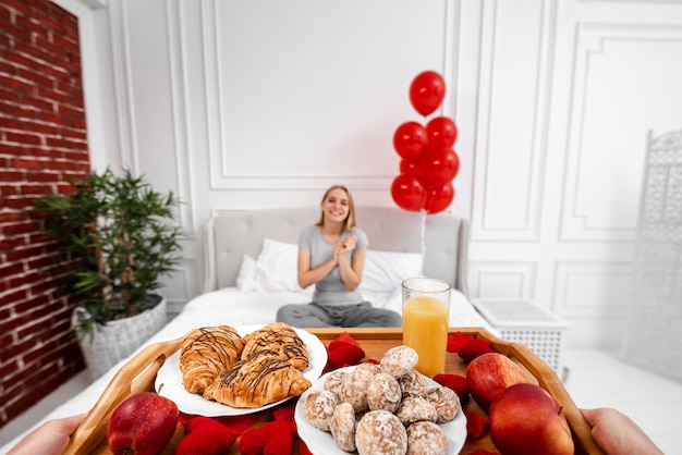 Close-up partner surprising woman with breakfast