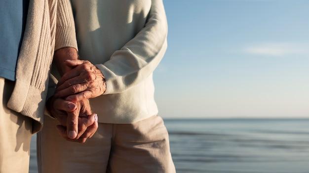 海辺で手をつないでいるパートナーをクローズアップ