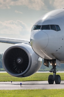 Close up of passenger airplane taxiing on the runway in summer day