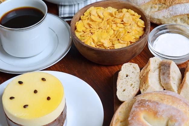 Close up of passion fruit cake, toast, coffee, yogurt, cereals.