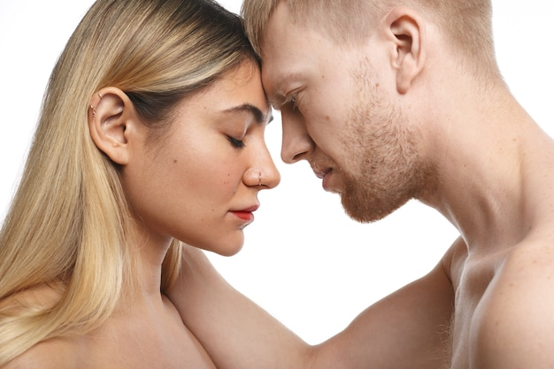 Close up passionate couple spending morning together: unshaven male holding his blonde female lover with facial piercing by her neck. people, love, passion and sexuality concept